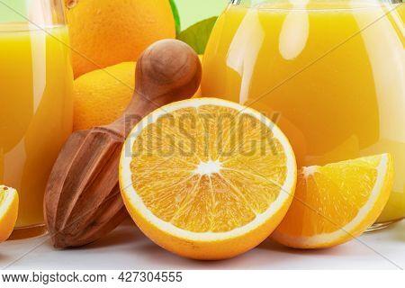 Yellow orange fruits and carafe of fresh orange juice isolated close up.