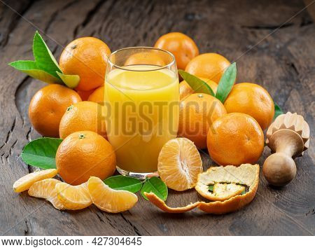 Orange tangerine fruits and glass of fresh tangerine juice on dark wooden background. Top view.