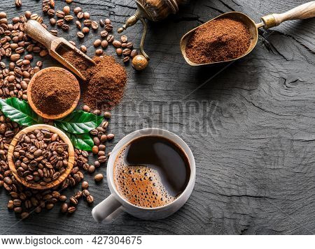 Roasted coffee beans, coffee cup  and ground coffee on wooden table. Top view.