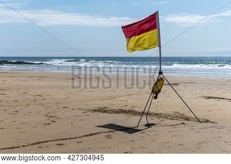 Beach Safety Flag On Sunny Day At Seaside