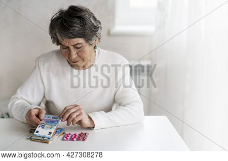 An Elderly 80 Year Woman, A Well-groomed Pensioner Considers Her Money And Expenses, And Saves Some