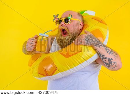 Fat Hungry Man With Wig In Head Is Ready To Swim With A Donut Lifesaver