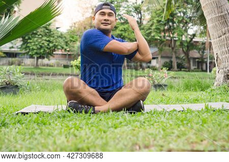 Fat Man In Sportswear Exercising Relaxing In Garden. Healthy Young Male Sitting Stretching Practicin