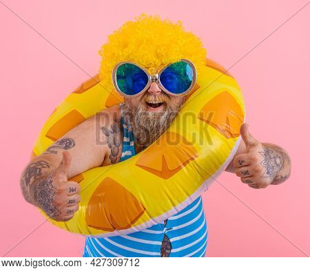 Fat Happy Man With Wig In Head Is Ready To Swim With A Donut Lifesaver