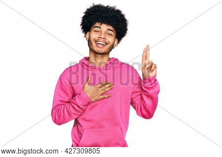 Young african american man with afro hair wearing casual pink sweatshirt smiling swearing with hand on chest and fingers up, making a loyalty promise oath
