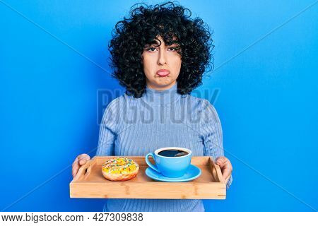Young middle east woman holding tray with doughnut and cup of coffee depressed and worry for distress, crying angry and afraid. sad expression.