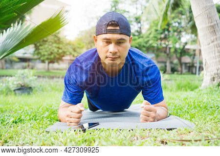 Man In Sportswear Plank Exercising Relaxing In Garden. Healthy Young Male Sitting Stretching Practic