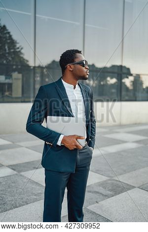Cool Black Businessperson With Laptop Against Building