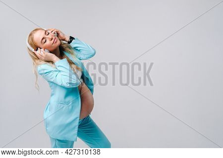 A Pregnant Woman In A Turquoise Suit With Headphones Stands And Listens To Music On A Gray Backgroun