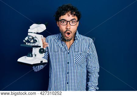 Young hispanic man holding microscope scared and amazed with open mouth for surprise, disbelief face