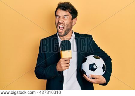 Handsome man with beard football reporter microphone angry and mad screaming frustrated and furious, shouting with anger. rage and aggressive concept.