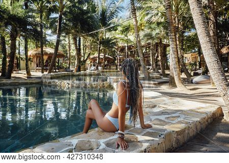 Backview Shot Of Woman Relaxing Around Swimming Pool