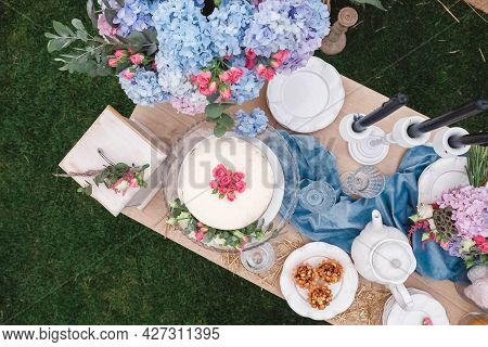 Banquet Dessert Table Decorated In A Rustic Style Decorated With Plates, Cutlery, Glasses, Candles A