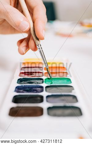 Close-up View Of Hand Holding A Brush And Mixing The Colors Of Paints On Palette. Concept Of Art Edu