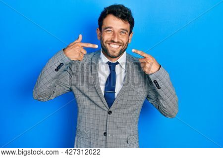 Handsome man with beard wearing business suit and tie smiling cheerful showing and pointing with fingers teeth and mouth. dental health concept.