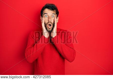 Handsome man with beard wearing casual red sweater afraid and shocked, surprise and amazed expression with hands on face
