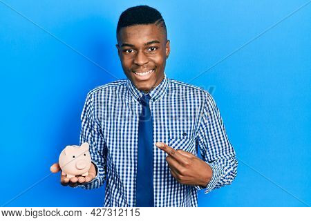 Young african american man wearing business clothes holding piggy bank smiling happy pointing with hand and finger