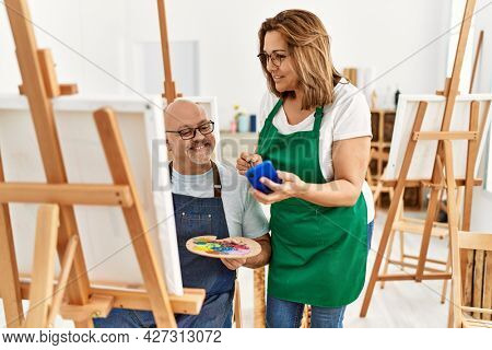 Middle age hispanic painter couple smiling happy painting and using smartphone at art studio.