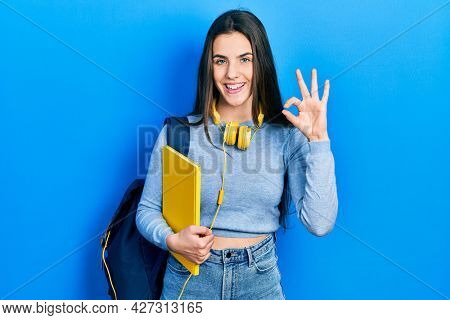 Young brunette teenager wearing student backpack and headphones doing ok sign with fingers, smiling friendly gesturing excellent symbol