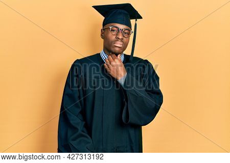 Young african american man wearing graduation cap and ceremony robe touching painful neck, sore throat for flu, clod and infection