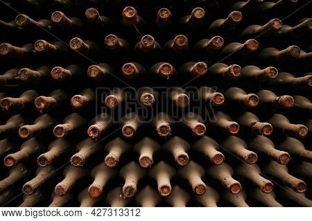 A Lot Of Old Wine Bottles Covered With Dust. Resting Wine Bottles Stacked On Wooden Racks In Cellar