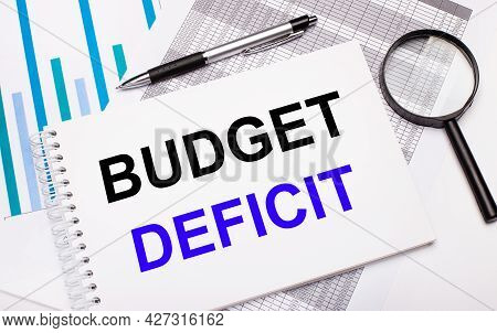 On The Table Are Reports, Diagrams, A Pen, A Magnifying Glass And A White Notepad With Budget Defici