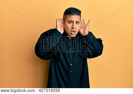 Young latin priest man standing over yellow background trying to hear both hands on ear gesture, curious for gossip. hearing problem, deaf