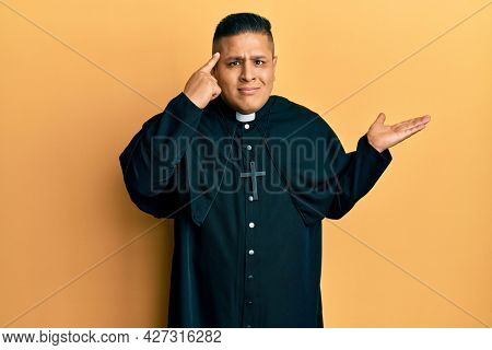 Young latin priest man standing over yellow background confused and annoyed with open palm showing copy space and pointing finger to forehead. think about it.