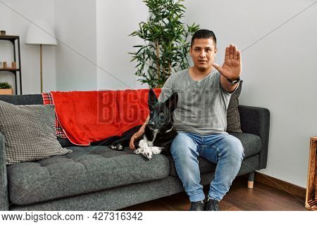 Young latin man and dog sitting on the sofa at home doing stop sing with palm of the hand. warning expression with negative and serious gesture on the face.