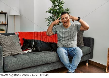 Young latin man and dog sitting on the sofa at home doing peace symbol with fingers over face, smiling cheerful showing victory