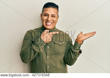 Young latin man wearing casual clothes amazed and smiling to the camera while presenting with hand and pointing with finger.