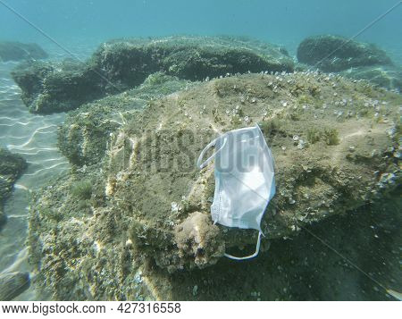 Discarded Surgical Face Mask Floating On Contaminated Sea Ecosystem, Covid19 Environment Pollution
