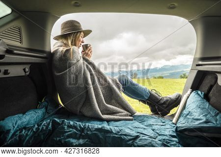 Girl resting in her car. Woman hiker, hiking backpacker traveler camper in sleeping bag, relaxing, drinking hot tea on top of mountain. Road trip. Health care, authenticity, sense of balance calmness.