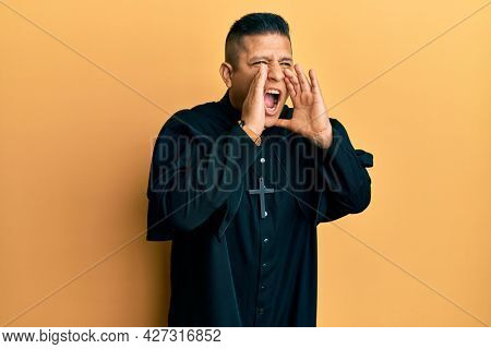 Young latin priest man standing over yellow background shouting angry out loud with hands over mouth