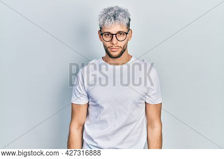 Young hispanic man with modern dyed hair wearing white t shirt and glasses relaxed with serious expression on face. simple and natural looking at the camera.