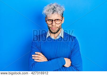 Young hispanic man with modern dyed hair wearing sweater and glasses skeptic and nervous, disapproving expression on face with crossed arms. negative person.