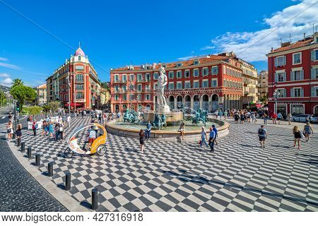 NICE, FRANCE - SEPTEMBER 03, 2018: People on Place Massena - main historic and famous city square in Nice with Fontaine du Soleil and Apollo statue in the center.