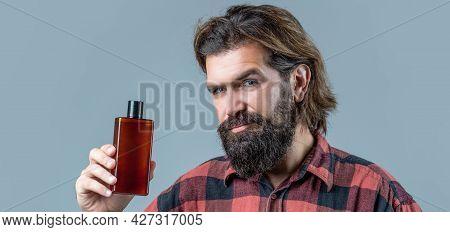 Handsome Man Applying Cream Lotion. Man Holds Bottle Of Shampoo Or Shower Gel. Shampoo Conditioner F