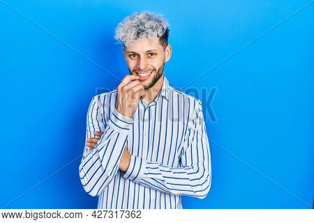 Young hispanic man with modern dyed hair wearing business striped shirt smiling looking confident at the camera with crossed arms and hand on chin. thinking positive.