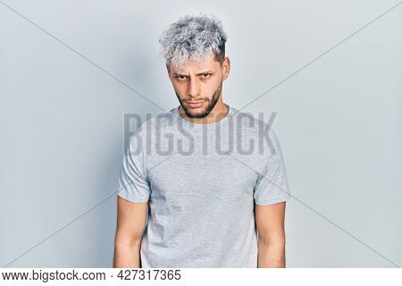 Young hispanic man with modern dyed hair wearing casual grey t shirt skeptic and nervous, frowning upset because of problem. negative person.
