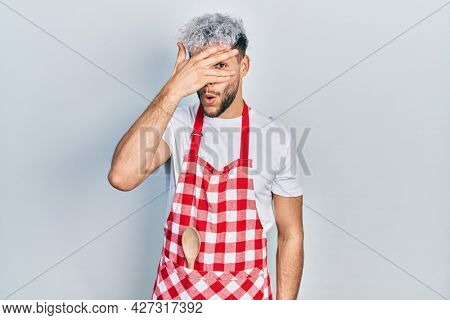Young hispanic man with modern dyed hair wearing apron peeking in shock covering face and eyes with hand, looking through fingers with embarrassed expression.
