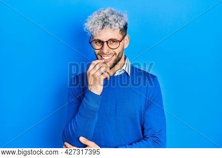 Young hispanic man with modern dyed hair wearing sweater and glasses looking confident at the camera with smile with crossed arms and hand raised on chin. thinking positive.
