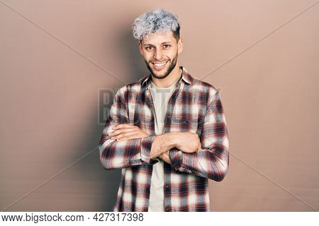 Young hispanic man with modern dyed hair wearing casual shirt happy face smiling with crossed arms looking at the camera. positive person.