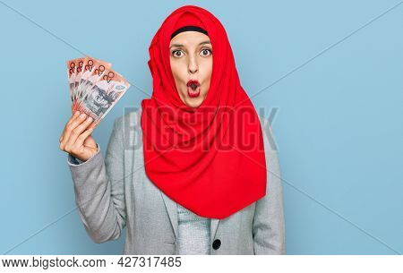 Beautiful hispanic woman wearing islamic hijab holding australian dollars banknotes scared and amazed with open mouth for surprise, disbelief face