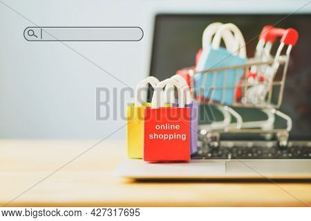 Small Red Shopping Paper Bag On Notebook And Blurred  Cart, Search Bar Beside With Copy Space, Onlin