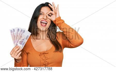 Beautiful hispanic woman holding russian 500 ruble banknotes smiling happy doing ok sign with hand on eye looking through fingers