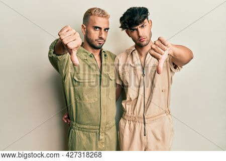 Homosexual gay couple standing together wearing casual jumpsuit looking unhappy and angry showing rejection and negative with thumbs down gesture. bad expression.