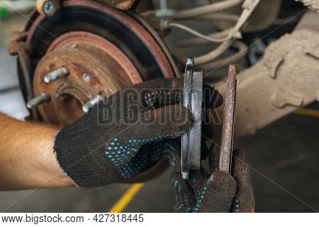 An Auto Mechanic Shows The Degree Of Wear Of An Old Brake Pad Compared To A New One Against The Back