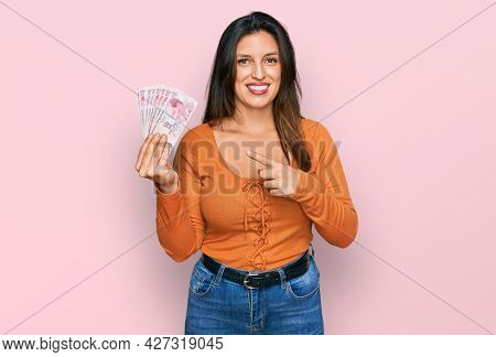 Beautiful hispanic woman holding 50 turkish lira banknotes smiling happy pointing with hand and finger