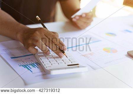 Young Businessman Or Professional Entrepreneur Using Calculator Paying Bills, Account Taxes Or Expen